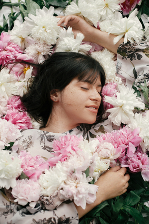Portrait of boho woman with natural makeup lying in peonies. Creative floral photo. Aroma and spa concept. International Womens Day. Beautiful brunette girl in many pink and white flowers