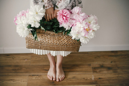 Boho girl holding pink and white peonies in rustic basket and standing barefoot on wooden floor. Stylish hipster woman in bohemian floral dress with peony flowers. International Womens Day Stock fotó