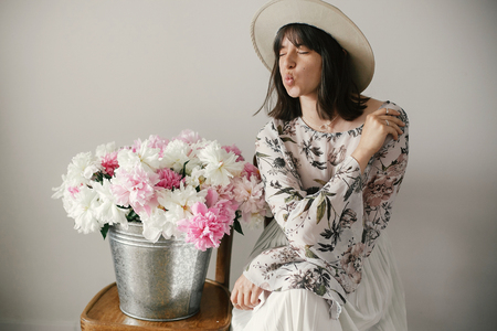 Stylish boho girl in hat sitting at metal bucket with peonies on rustic wooden chair.Beautiful hipster woman kissing   at big peonies bouquet. Countryside living. International Womens Day