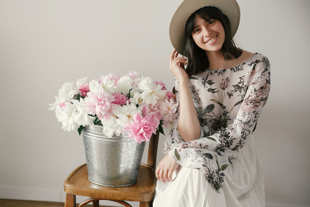 Stylish boho girl in hat sitting at metal bucket with peonies on rustic wooden chair.Beautiful hipster woman smiling  at big peonies bouquet. Countryside living. International Womens Day
