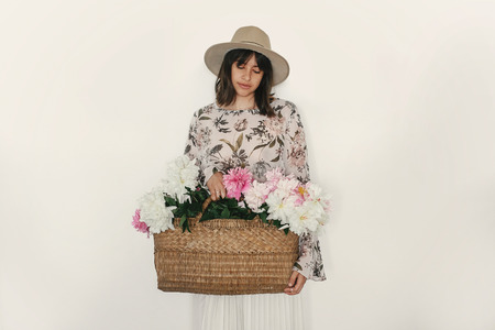 Sensual portrait of boho girl holding pink peonies in rustic basket, isolated on white. Stylish hipster woman in hat and bohemian floral dress posing with flowers. International Womens Day.