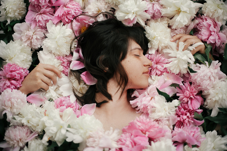 Beautiful brunette girl lying in many pink and white peonies. Boho woman portrait with natural makeup in peony flowers. Creative floral photo. Aroma scent concept. International Womens Day Stock fotó