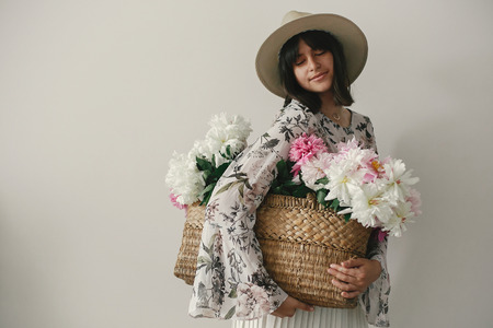 Sensual portrait of boho girl holding pink and white peonies in rustic basket. Stylish hipster woman in hat and bohemian floral dress posing with flowers. International Womens Day. Stock fotó