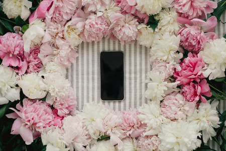 Phone with empty screen in peonies frame flat lay on rustic table cloth. Space for text. Greeting card mockup. Happy mothers day. International Womens Day. Valentines day.