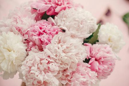 Stijlvol pioenrozenboeket plat gelegd. Roze en witte pioenrozen op pastelroze papier. Hallo lente. Gelukkige moederdag, bloemengroetkaartmodel. Internationale Vrouwendag. Valentijnsdag Stockfoto