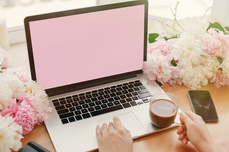 Girl hands on stylish laptop with empty screen and coffee, phone, black notebook and peonies on rustic wooden table. Freelance concept. Workplace. Space for text.  Women's Day.