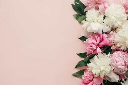 Día Internacional de la Mujer. Peonías con estilo plano laical. Borde de peonías rosas y blancas sobre papel rosa pastel con espacio para texto. Feliz día de la madre, maqueta de tarjeta de felicitación floral. Día de San Valentín.