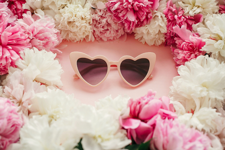Stylish heart shape pink sunglasses with pink and white peonies on pastel pink paper. Stylish hello summer image. International Womens Day. Valentines day. Summer vacation Stockfoto