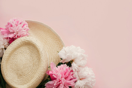 Hello spring image with copy space. Summer vacation concept. Straw hat with white and pink peonies on pastel pink paper, flat lay.  International Womens Day. Happy mothers day