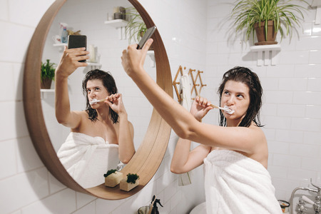 Young happy woman in white towel making selfie while brushing teeth and looking at phone in stylish bathroom at round mirror. Social media affect. Tooth care concept Stock Photo