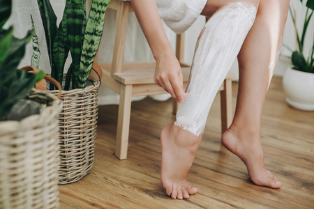 Hair Removal concept, depilation process. Young woman in white towel applying shaving cream on her legs and holding holding plastic razor in home bathroom with green plants. Skin care 스톡 콘텐츠