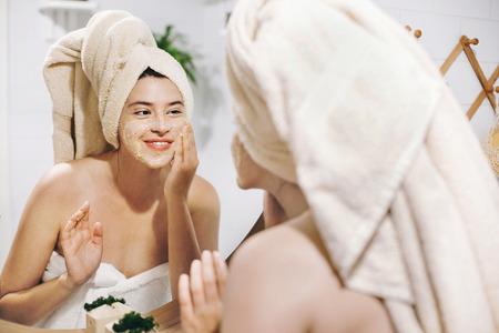 Hautpflege-Konzept. Junge glückliche Frau im Handtuch, die Gesichtsmassage mit organischem Gesichtspeeling macht und Spiegel im stilvollen Badezimmer betrachtet. Mädchen, das Peeling-Creme auftragen, die Haut schälen und reinigen