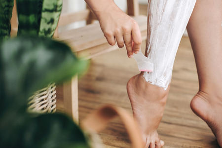 Hair Removal concept, depilation process. Young woman in white towel applying shaving cream on her legs and holding holding plastic razor in home bathroom with green plants. Skin care 版權商用圖片