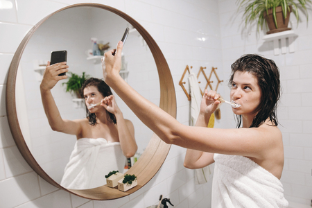Social media affect. Young happy woman in white towel making selfie while brushing teeth and looking at phone in stylish bathroom at round mirror. Slim sexy woman with natural skin