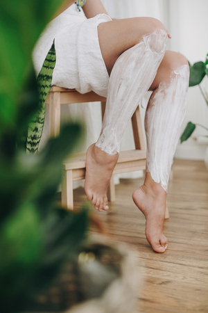 Young woman in white towel applying shaving cream on her legs in home bathroom with green plants. Skin care and wellness. Hair Removal concept, depilation cream.