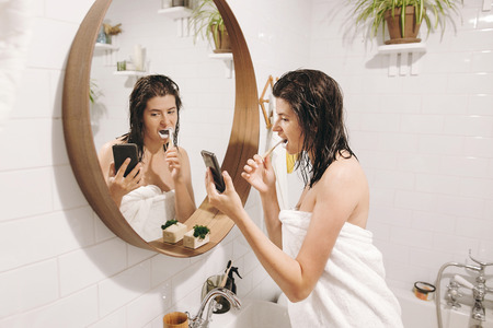 Young happy woman in white towel brushing teeth and looking at smartphone in bathroom with mirror. Slim sexy woman with natural skin and wet hair daily routine after shower. Social media affect