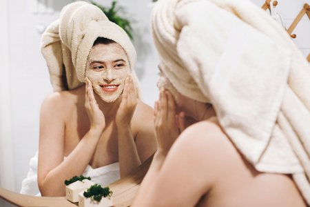 Young happy woman in towel making facial massage with  organic face scrub and looking at mirror in stylish bathroom. Girl applying scrub cream, peeling and cleaning skin. Skin Care