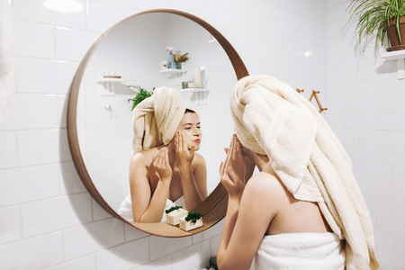 Young happy woman in towel making facial massage with  organic face scrub and looking at mirror in stylish bathroom. Girl applying scrub cream, peeling and cleaning skin. Skin Care Banque d'images - 116123869