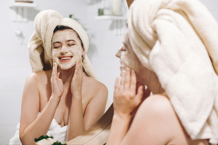 Young happy woman in towel applying organic face mask and looking at round mirror in stylish bathroom. Girl making facial massage with scrub, peeling and cleaning skin on face. Skin Care