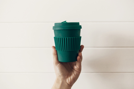 Ban single use plastic. Hand holding stylish reusable eco coffee cup on white wooden background. Green Cup from natural  bamboo fiber, zero waste concept. Make a choice. Take away coffee 免版税图像