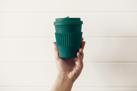 Zero waste concept. Hand holding stylish reusable eco coffee cup on white wooden background. Green Cup from natural  bamboo fiber. Ban single use plastic. Make a choice.