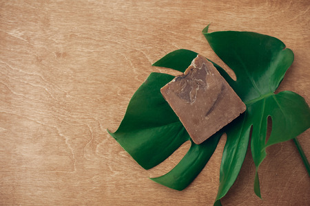 Natural soap on wooden background with green monstera leaf. Plastic free beauty essentials. Zero waste concept, flat lay with copy space. Sustainable lifestyle Stock Photo