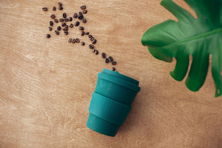 Stylish reusable eco coffee cup  on wooden background with roasted coffee beans and green monstera leaf. Ban single use plastic, zero waste concept, flat lay. Sustainable lifestyle.
