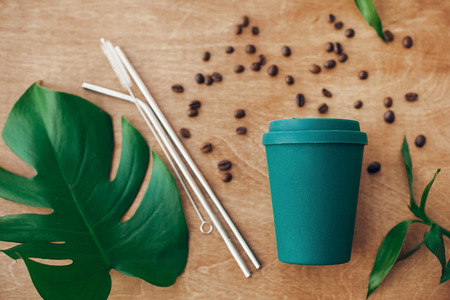 Stylish reusable eco coffee cup and metallic steel straws on wooden background with green monstera and bamboo leaves, flat lay. Ban single use plastic, zero waste concept. Sustainable lifestyle Фото со стока
