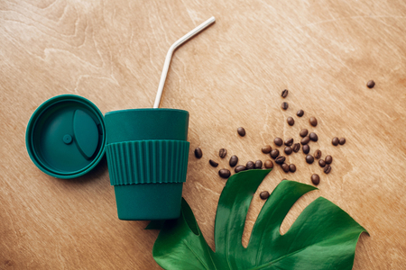 Zero waste concept, flat lay. Stylish reusable eco coffee cup and metallic steel straws on wooden background with green monstera leaf. Ban single use plastic. Sustainable lifestyle