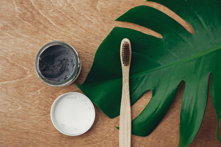 Natural toothpaste activated charcoal and bamboo toothbrush on wooden background with green monstera leaf. Plastic free beauty essentials, teeth care. Zero waste concept. Sustainable lifestyle