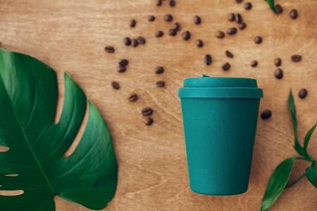 Stilvolle wiederverwendbare Öko-Kaffeetasse auf Holzhintergrund mit gerösteten Kaffeebohnen und grünem Monstera-Blatt. Verbot von Einwegplastik, Zero-Waste-Konzept, flache Lage. Nachhaltiger Lebensstil.