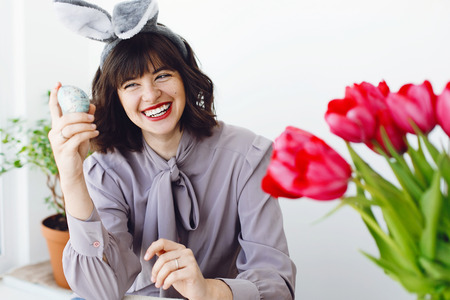 Beautiful young woman in bunny ears painting easter egg and smiling at table with paint, brushes, tulips in vase. Happy girl decorating egg, holding brush, easter holiday preparations