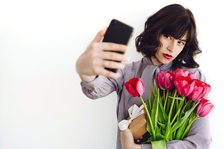 Beautiful brunette girl holding bouquet of tulips and gift box and taking selfie on white background indoors, space for text. Stylish young woman with flowers and phone. Happy mothers day