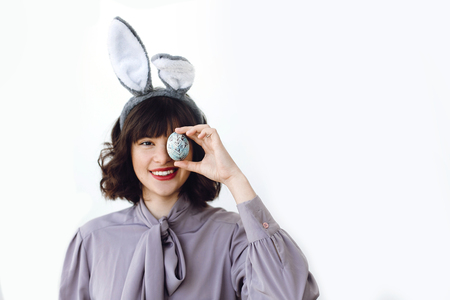 Happy Easter greetings. Beautiful young woman in bunny ears smiling and holding easter egg near face on white background indoors, space for text. Easter hunt concept.