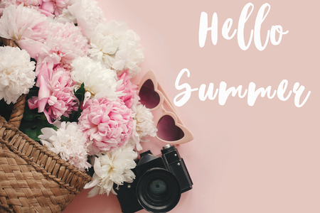 Hello Summer text sign on stylish photo camera, retro sunglasses, rustic bag with peonies on pastel pink paper. Summer vacation and travel concept, girly image