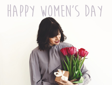 Happy Womens Day text sign and beautiful girl holding stylish bouquet of tulips and gift box on white background. Greeting card. International womens day 8 march 版權商用圖片