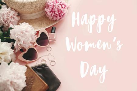 Happy Women's Day segno di testo a eleganti occhiali da sole retrò rosa girly, peonie, gioielli, cappello, borsa, cosmetici su carta rosa pastello piatta. Potere della ragazza. Giornata internazionale della donna, 8 marzo