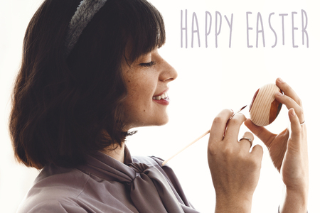 Happy Easter text sign and beautiful young  woman in bunny ears painting easter egg in light white background. Easter hunt concept. Easter Greetings