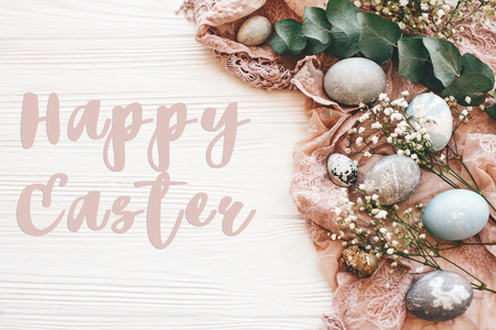 Happy Easter text sign on stylish easter eggs with spring flowers and eucalyptus on rustic fabric on white wooden table, flat lay. Easter greetings card Archivio Fotografico