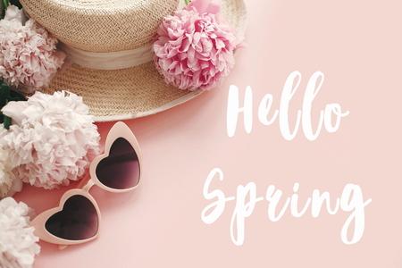 Hello Spring text sign on stylish girly pink retro sunglasses, white and pink peonies, straw hat on pastel pink paper, flat lay. Stylish floral greeting card.
