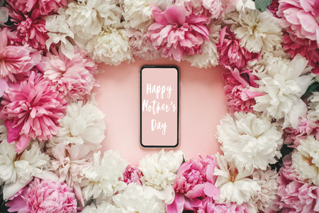 Happy Mother's Day text sign on screen phone with pink and white peonies on pastel pink paper, flat lay. Stylish floral greeting card.