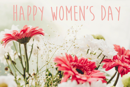 Happy Women's Day text sign at pink gerbera,white daisy and green chrysanthemum  bouquet at rustic window in soft light. Girl Power. International womens day, 8 march.
