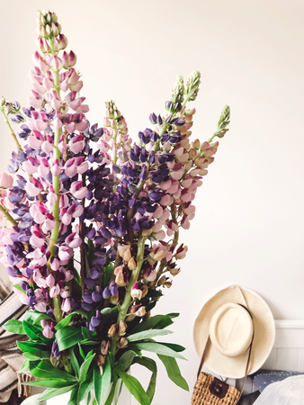 Stylish pink and purple lupine in vase on background of trendy straw bag and hat on stylish white bed. Hello spring. Happy Mothers day. Countryside living Stock Photo