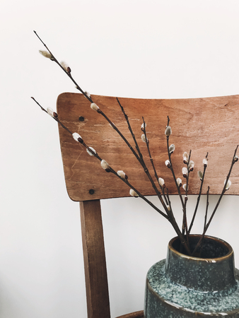 Simple willow buds branches in stylish vase on wooden rustic chair in home. Hello spring concept. Countryside living. Modern rural still life. Easter decorations Stock Photo