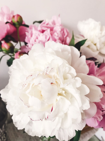 Beautiful big white peony and pink peonies in vase on stylish nightstand. Hello spring. Happy Mothers day