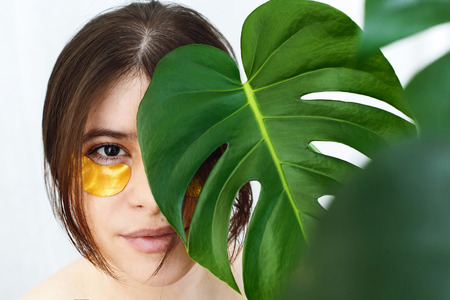 Girl with natural skin and lifting anti-wrinkle collagen patches under eyes and green palm leaf. Portrait of beautiful young woman with golden eye patches on white, copy space.  Eye Skin Care