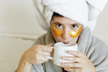 Happy girl drinking coffee and applying eye patches, skin care and relax. Beautiful young woman with golden eye patches in bathrobe holding cup of coffee and lying in bed, enjoying morning routine.