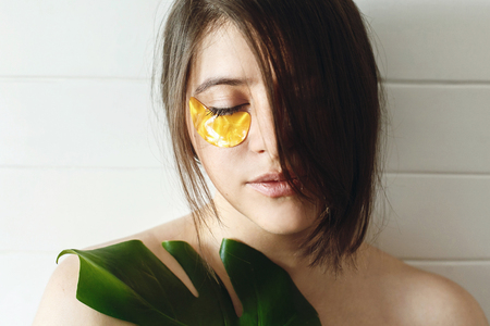 Portrait of beautiful young woman with natural makeup and golden eye patches at green monstera leaf. Natural skin care. Lifting anti-wrinkle collagen patches under eyes. Eye Skin Care and Treatment.