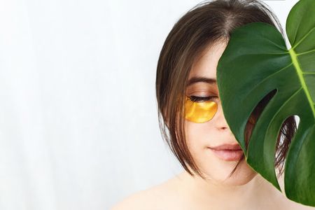 Portrait of beautiful young woman with golden eye patches at green monstera leaf on white background, copy space. Natural skin care. Lifting anti-wrinkle collagen patches under eyes. Eye Skin Care Stock Photo