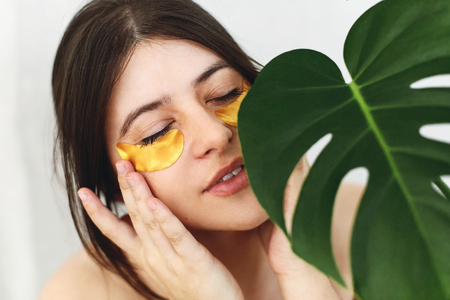 Portrait of beautiful young woman applying golden eye patches on fresh soft skin at green palm leaf on white. Happy girl with lifting gel anti-wrinkle collagen patches under eyes. Beauty Cosmetics Stock Photo